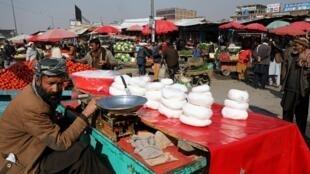Un homme vendant du fromage attend des clients sur un marché à Kaboul, le 22 février 2020
