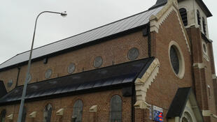 Solar panels cover the roof of the St Vaast church in Loos-en-Gohelle, producing green energy for Enercoop