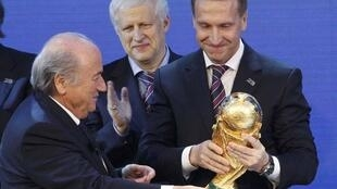 FIFA president Sepp Blatter (L) hands over a copy of the World Cup to Russia's Deputy Prime Minister Igor Shuvalov.