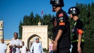 Des policiers chinois surveillent la sortie de la mosquée de Kashgar, dans la région du Xinjiang où vit la minorité musulmane ouïghoure. (Image d'illustration)