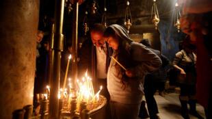 Cristianos encienden velas en la iglesia de la Natividad en Belén, Cisjordania, el 3 de diciembre de 2016.