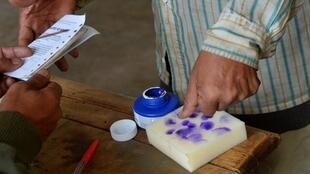 Un votant trempe son pouce dans l'encre après avoir mis son bulletin dans l'urne lors de l'élection présidentielle de 2013. (Image d'illustration)