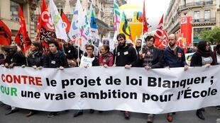 """Protesters hold a banner reading """"Against the Blanquer bill; For a real ambition for school"""" during a demo on 4 April, 2019, in Paris."""