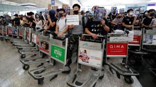 Les manifestants pro-démocratie obstruent les allées menant aux zones d'embarquement des deux terminaux avec des chariots à l'aéroport international de Hong Kong, le 13 août 2019.