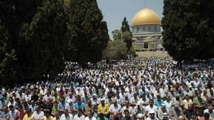 Palestinian men pray in front of the Dome of the Rock on the compound known to Muslims as Noble Sanctuary