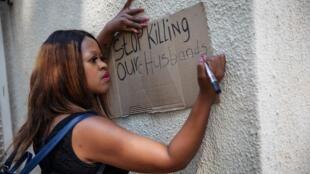 """Joanesburgo, na África do Sul, também foi palco de marchas contra a xenofobia este sábado, 14 de Setembro de 2019. Esta senhora escreve no cartaz """"Párem de matar os nossos maridos."""""""