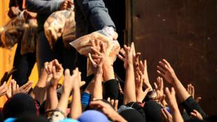 Distribution de pain aux déplacés de Mossoul du camp de Hammam al-Alil, au sud de la ville, le 14 mars 2017.