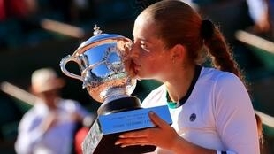 Jelena Ostapenko beija o troféu Suzanne Lenglen conquistado na final de Roland Garros.