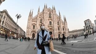 Une femme sur la Piazza del Duomo dans le centre de Milan porte un masque de protection contre l'épidémie du coronavirus, le 24 février 2020.