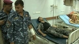 A wounded policeman stands near another lying on a hospital bed in Baghdad, 24 April 2011