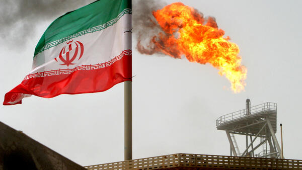Uma tocha de gás em uma plataforma de produção de petróleo nos campos de petróleo de Soroush é vista ao lado de uma bandeira iraniana no Golfo Pérsico, Irã, em 25 de julho de 2005.