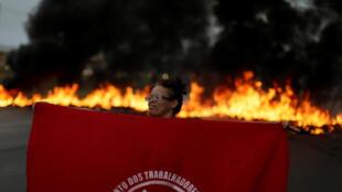 Manifestante del Movimiento de los Trabajadores sin Techo sostiene una bandera frente a una barricada en llamas, el 28 de abril de 2017 en Brasilia.