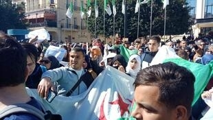 Algerians march with a national flag during a protest rally against ailing President Abdelaziz Bouteflika's bid for a fifth term in power, in the northeastern city of Annaba on March 3, 2019.