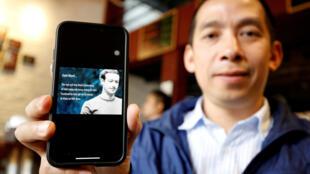 Lã Việt Dũng, có tài khoản Facebook, giương bức thư ngỏ mà ông đã ký gửi lãnh đạo Facebook Mark Zuckerberg. (Ảnh chụp tại Hà Nội, ngày 10/04/2018)