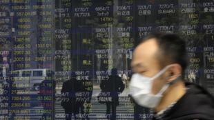 Un transeúnte con mascarilla pasa frente a un panel de cotizaciones de la Bolsa de Tokio, el 26 de marzo de 2020 en la capital japonesa