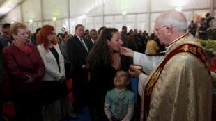 El enviado personal del Papa, el cardenal Fernando Filoni, imparte la comunión durante la misa de Pascua, Erbil, 4 de abril de 2015.