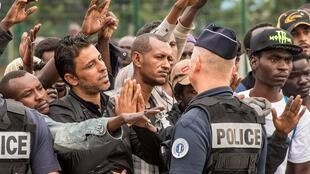 Migrants waiting to be transferred from the Jungle to centres elsewhere in France