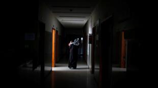 Plaestina carrega seu filho em hospital sem eletricidade de Gaza, 6 de fevereiro de 2018.
