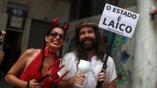 Deux participants portant une pancarte «L'État est laïc» lors des festivités du carnaval de Rio, au Brésil, le 16 février 2020.