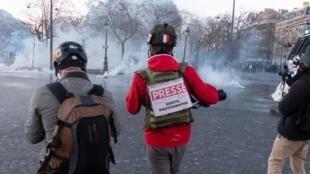 Photographe de presse avec une affichette «PRESSE, GENTIL PHOTOGRAPHE» lors de la manifestation de l'acte 18 des «gilets jaunes», le 16 mars 2019 à Paris.