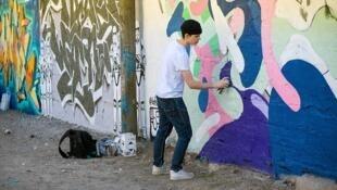 Mineur en train de taguer un mur.