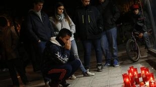 Jovem levam velas ao estádio Madri Arena, onde aconteceu festa de Halloween que terminou em tragédia.