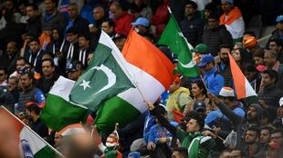 Spectators wave national flags after the 2019 Cricket World Cup group stage match between India and Pakistan at Old Trafford in Manchester, northwest England, on June 16, 2019.