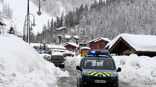 A police car drives through the village of Val d'Isere, as the precautions are put into place for motorists due to an avalanche alert in the French Alpes on January 9, 2018.