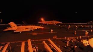 Caças americanos se preparam na pista de decolagem de um porta-aviões para bombardear o Estado Islâmico
