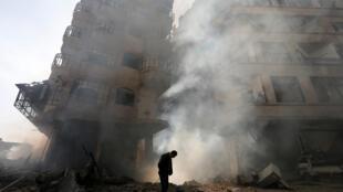 Un homme devant un immeuble désaffecté en feu après une frappe aérienne de l'armée syrienne, dans le quartier Ain Tarma de Damas.
