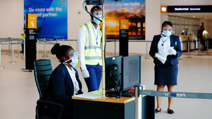 Les agents de santé scannent les voyageurs dans le cadre de la procédure de dépistage des coronavirus à l'Aéroport international de Kotoka à Accra, au Ghana, le 30 janvier 2020.