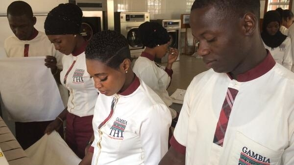 Students concentrate on the linen pressing machine at the training institute.