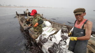 Clean-up workers near the Dalian spill