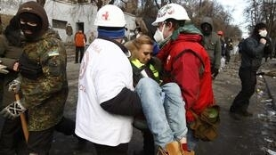 Medical volunteers carry a wounded journalist at the site of clashes with riot police in Kiev, 20 January, 2014
