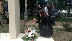 Apollonia, the daughter of Claude Verlon, viewing her father's name on a monument dedicated to journalists killed in war, in October 2014