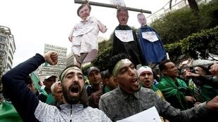 People carry a mock hangman with the faces of Algerian businessman Ali Haddad, former prime minister Ahmed Ouyahia, and Said Bouteflika in Algiers, Algeria