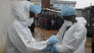 Agentes sanitários preparam-se para analisar o cadáver de uma vítima de ébola, Monrovia, 17 de Agosto de 2014.
