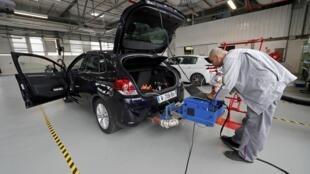 A technician uses a portable emissions measurement system on a PSA Citroën car