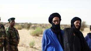 Des soldats maliens à côté de Touaregs.