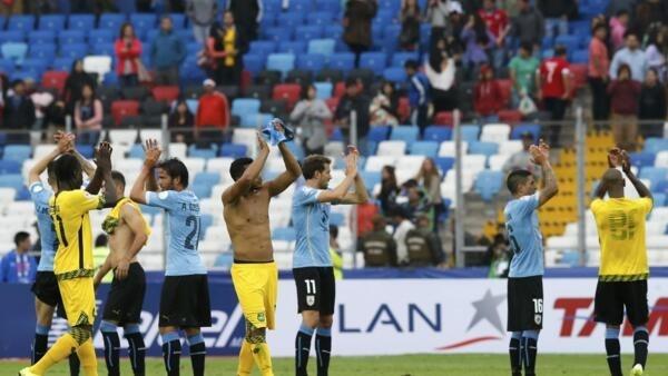 Seleções do Uruguai e da Jamaica aplaudem torcida depois do término do encontro.