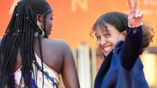 L'actrice et réalisatrice française Mati Diop fait signe, alors qu'elle arrive avec l'actrice sénégalaise Mama Sane pour la projection du film «Atlantique» à la 72ème édition du Festival de Cannes.