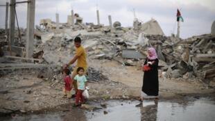 Palestinos caminham ao lado de ruínas de casas no campo de Khan Younis, Gaza, 18 de agosto de 2014.