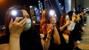 Manifestantes iluminam seus smartphones enquanto formam uma cadeia humana durante uma manifestação para pedir reformas políticas no distrito central de Hong Kong, China, 23 de agosto de 2019.