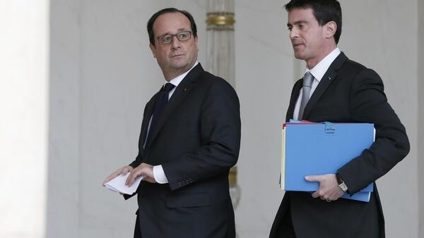 French President Francois Hollande (L) and Prime Minister Manuel Valls walk together after the weekly cabinet meeting at the Elysee Palace in Paris December 22, 2014