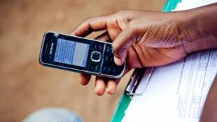 Un agent de la Croix-Rouge utilise le téléphone cellulaire pour transmettre des informations destinées à combattre le paludisme au Nigeria.