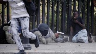 Un homme en uniforme de la police nationale haïtienne avec son arme lors de la fusillade au Champ de Mars à Port-au-Prince le 23 février 2020.