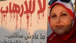 Une femme tunisienne porte un panneau sur lequel on peut lire : «Non au terrorisme», en lettres de sang, à Tunis, le 19 mars 2015.