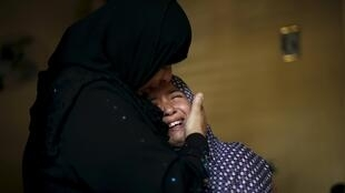 Parentes de mulher e criança palestinas mortas choram ao verem os corpos das vítimas.