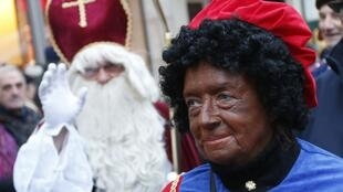 Saint Nicholas waves next to one of his assistants called Black Pete during a traditional parade in Brussels
