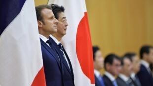 Tổng thống Pháp Emmanuel Macron (T) duyệt hàng quân danh dự cùng với thủ tướng Nhật Shinzo Abe tại Tokyo, ngày 26/12/2019.